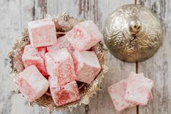 Rose flavoured turkish delight in traditional silver bowl on wooden white bac Stock Photos