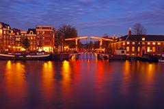 Amsterdam by night in the Netherlands at the Amstel - stock photo