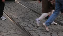 Tram tracks in cobble stone road with people walking across Stock Footage