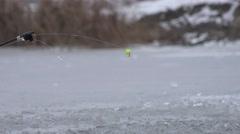 Fishing rod  river in winter on ice near hole 4k Stock Footage