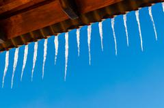 Icicles on the roof against the blue sky Stock Photos
