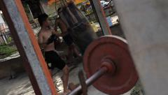 Teenage Muay Thai Fighter in Gym Punch Bag Kicking Weights Thailand Hand Held - stock footage