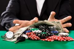 Poker player with chips and money at casino table Stock Photos