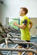 Smiling man exercising on treadmill in gym Stock Photos