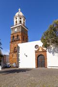 famous clock tower and church of nuestra senora de guadalupe in teguise, lanz - stock photo