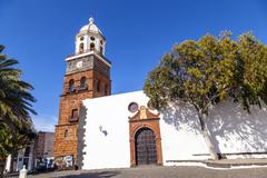Famous clock tower and church of nuestra senora de guadalupe in teguise, lanz Stock Photos