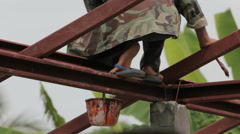 Man painting metal bar on the roof Stock Footage
