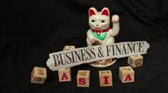 LUCKY ASIAN CAT - Dolly shot waving cat holds news headline Stock Footage