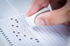 Hand erase wrong answer on  exam carbon paper computer sheet Stock Photos