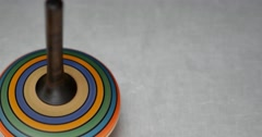 Footage of a colorful spinning top twisting on a metal table Stock Footage
