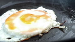 Closeup of greasy fried egg on frying pan with cooking audio - stock footage
