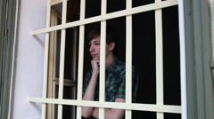 Young man behind the bars, depressed, teenage boy, orphanage, orphan Stock Footage