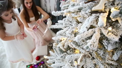 Mother and little daughter decorate a Christmas tree - dolly shot Stock Footage