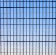 fence with grid structure with blue sky in background - stock photo