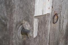 Old run-down wooden door and wooden lock out of focus - stock photo