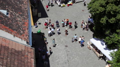 Aerial view time lapse of a group of tourists with tour guide in a market square Stock Footage