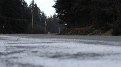 Car Passing in Early Winter Conditions with Headlights Stock Footage