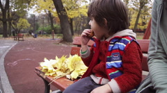 Boy sitting on the bench and eating biscuit, steadycam shot, slow motion 240fps Stock Footage
