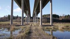 Drone slow tracking shot flight under the bridge in sun set Stock Footage