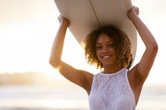 mixed-race woman holding a surfboard at sunset - stock photo