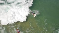 Stunning aerial drone shot of surfer catching wave in Rio de Janeiro - stock footage