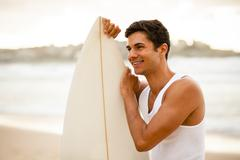 Young surfer standing with his surfboard Stock Photos