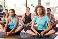 multi-ethnic group stretching in a gym - stock photo