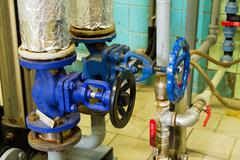 closeup of pipes and faucet valves of heating system in a boiler room - stock photo