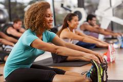 Young woman stretching in a gym Stock Photos