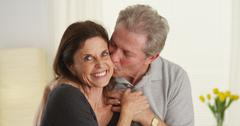 cute senior couple smiling and looking at camera - stock photo