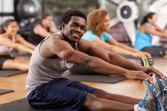 Young african-american man stretching in a gym Stock Photos