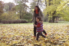 Son and mother walking in the park, steadycam shot, slow motion shot Stock Footage