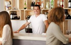 Happy young barman in a bar Stock Photos