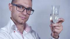 Young handsome man in white shirt celebrate with champagne over grey background. Stock Footage