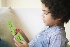 Mixed race boy using flash cards to study math Stock Photos