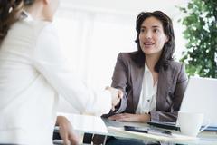 Hispanic businesswomen shaking hands in office Stock Photos