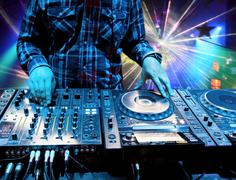 Dj mixes the track in the nightclub at a party. in the background laser light Stock Photos