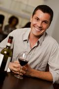 young man with a glass of wine in a restaurant - stock photo
