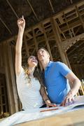 Caucasian couple pointing at ceiling under construction Stock Photos