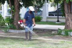 blurred image of a man mowing the grass in public park - stock photo