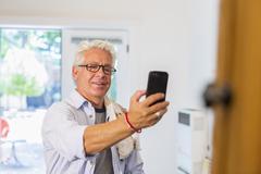 Older Hispanic artist taking cell phone photograph of art in studio Stock Photos