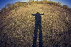 Fish-eye lens view of shadow of man in field Stock Photos