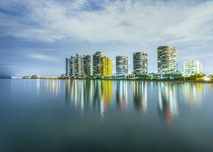 skyline of miami sunny isles by night with reflections at the ocean - stock photo
