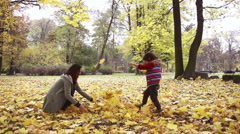 Boy and his mother playing with leaves, slow motion shot at 240fps Stock Footage
