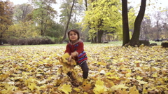 Boy throwing leaves in the air, steadycam shot, slow motion shot at 240fps Stock Footage