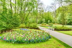 Spring garden with blooming flowers and trees Stock Photos
