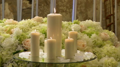 Close-up of lighted candles on flowers background Stock Footage