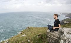 man sitting on a rock on a grass hill cliff overlooking the sea at tintagel c - stock photo