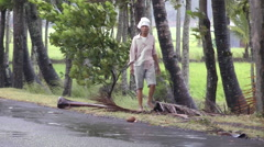 Filipino woman picking up fallen debri during typhoon Hagupit in Philippines Stock Footage