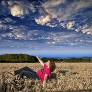 young female looking up at the upside down clouds pretending to fly in an air - stock photo